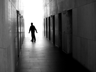 lone man in a hallway with closed doors